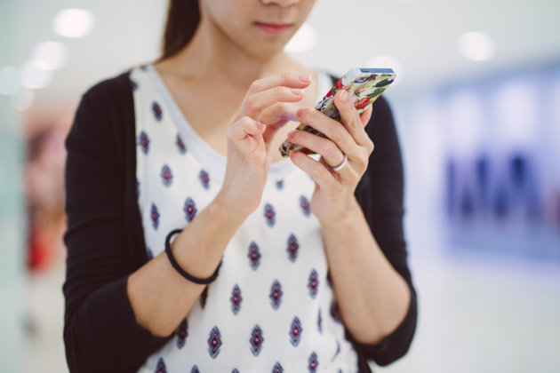 Young lady using smartphone in mall