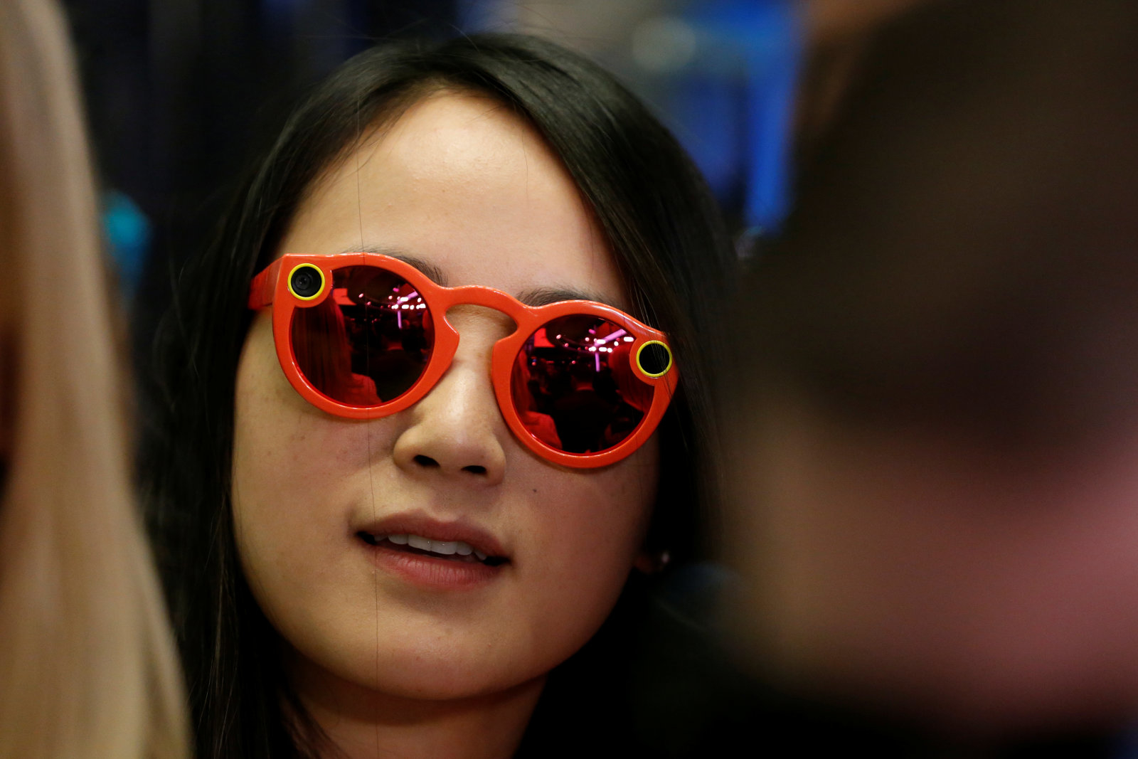 A woman wears Snapchat Spectacles on the floor of the New York Stock Exchange (NYSE) while waiting for Snap Inc. to list their IPO in New York, U.S., March 2, 2017.  REUTERS/Lucas Jackson
