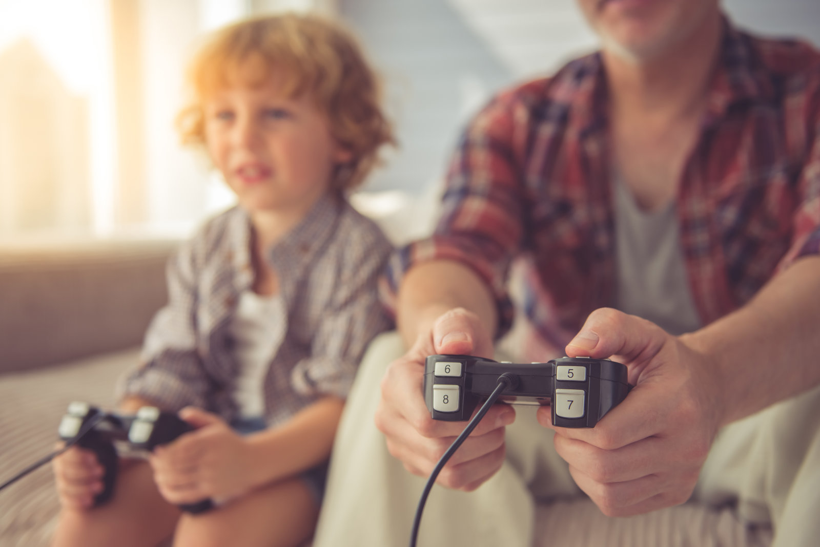 Cropped image of handsome grandpa and grandson playing game console while spending time together at home