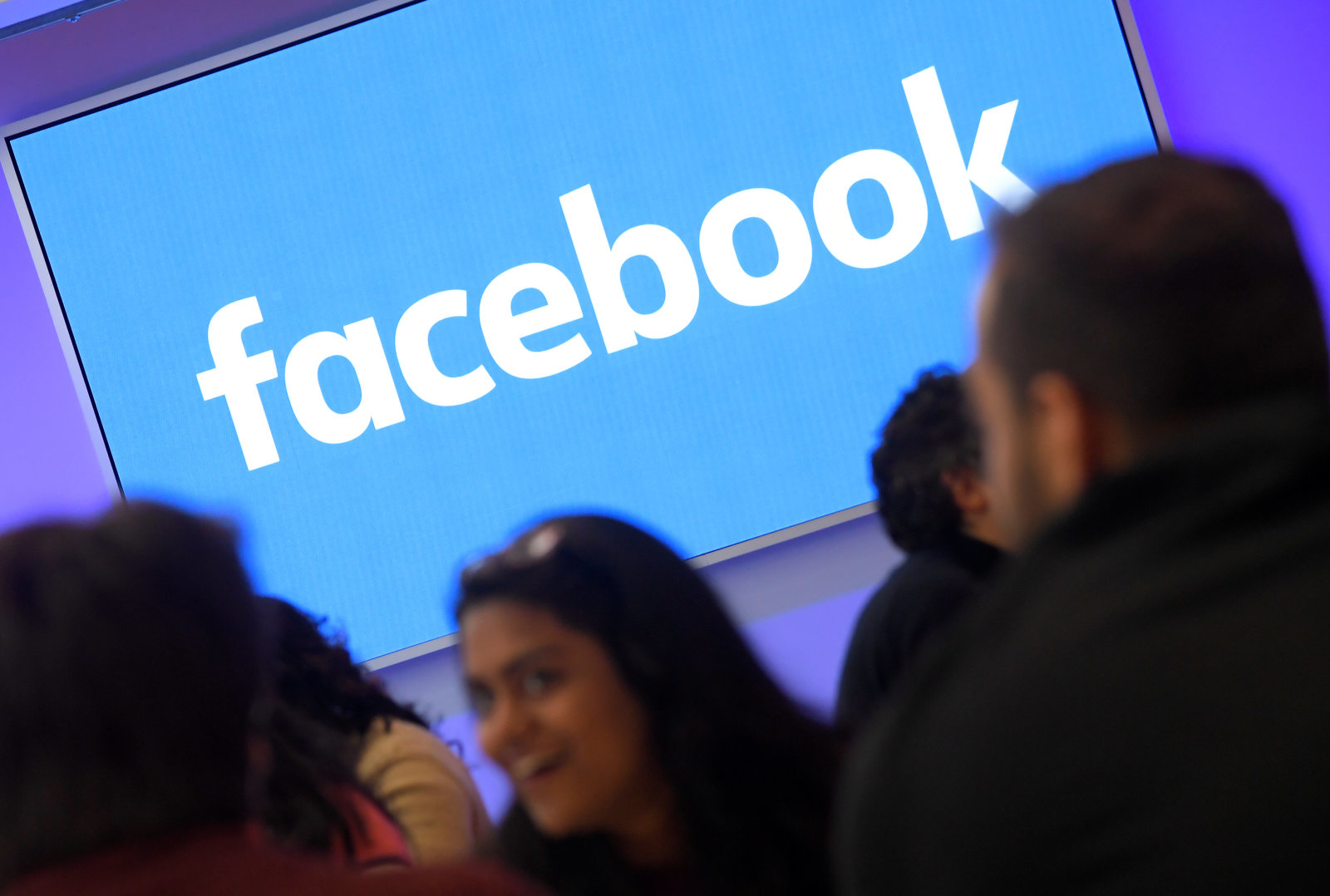 People stand in front of a logo at Facebook's headquarters in London, Britain, December 4, 2017. REUTERS/Toby Melville