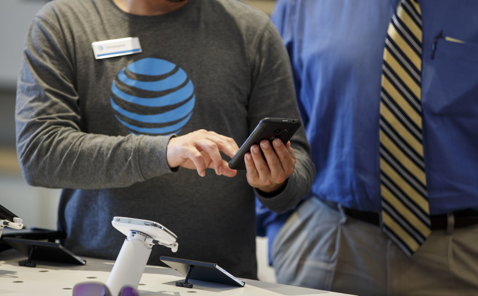 An employee helps a customer with a smartphone at an AT&T Inc. store in Newport Beach, California, U.S., on Thursday, Aug. 10, 2017. AT&T Inc. shares surged the most in more than eight years after the telecommunications giant posted a surprise wireless subscriber gain in the second quarter, showing it can fend for itself in a cutthroat price war. An offer for unlimited wireless data, bundled with discounted streaming-TV service, helping AT&T bide its time while awaiting regulatory approval to transform into a media powerhouse through the $85.4 billion purchase of Time Warner Inc. Photographer: Patrick T. Fallon/Bloomberg via Getty Images