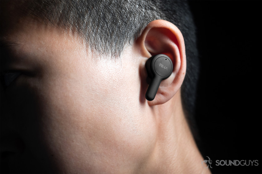 RHA TrueConnect: The left earbud being worn by a woman, it protrudes a bit from the ear with the stem angled downward.