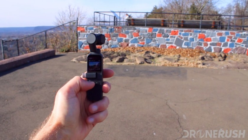 The DJI Osmo Pocket in a man's left hand held up outside to photograph a colorful wall.