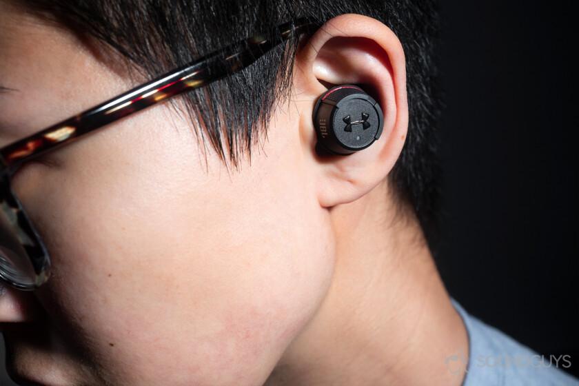 Under Armour True Wireless Flash JBL: A woman wearing the earbuds.