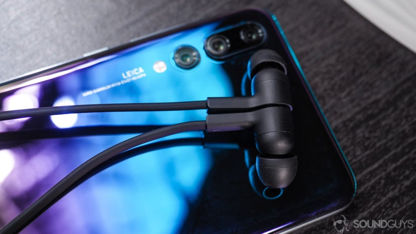 Huawei Freelace: close-up of earbuds magnetized together atop Huawei P20 smartphone.