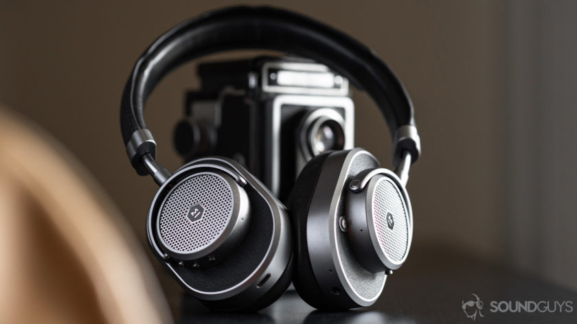 Master & Dynamic MW65: Headphones angled and leaning against a vintage camera.
