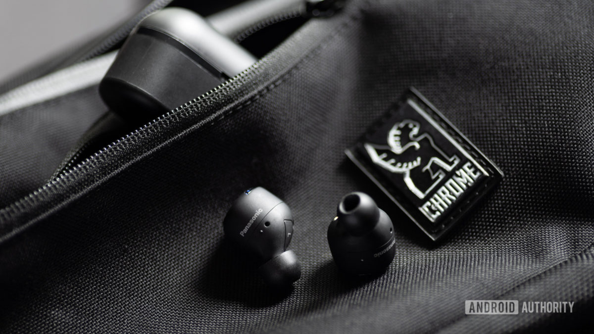 A picture of the Panasonic RZ-S500W noise cancelling earbuds on a Chrome sling bag with the case angled in the zippered pocket of the bag.