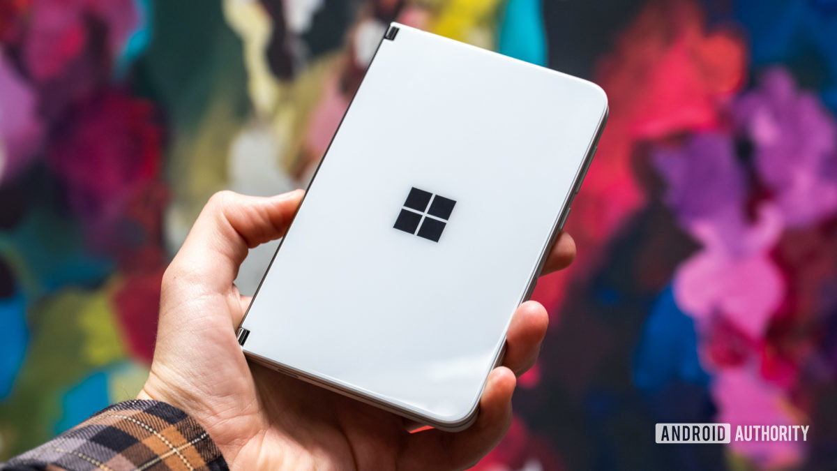Microsoft Surface Duo closed in hand against backdrop