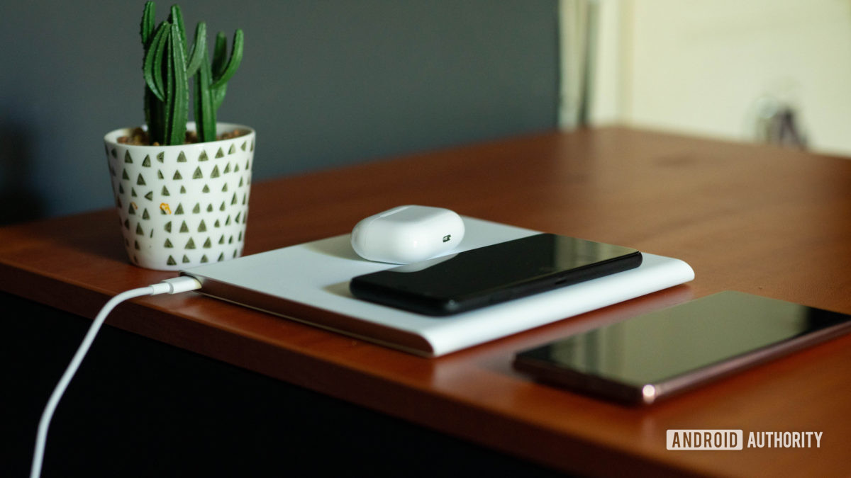 Xiaomi Mi 20W Smart Tracking Wireless Charging Pad with phones and earphones on it with the cable on show