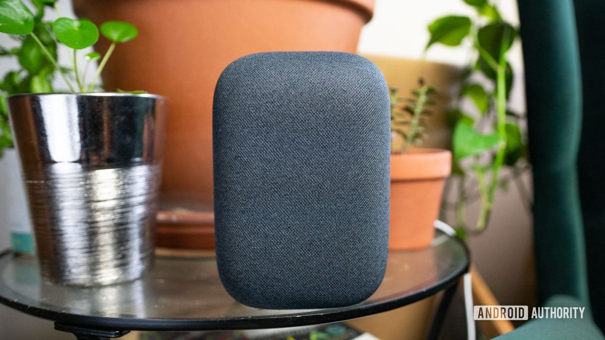 Google Nest Audio pictured on glass table with plants