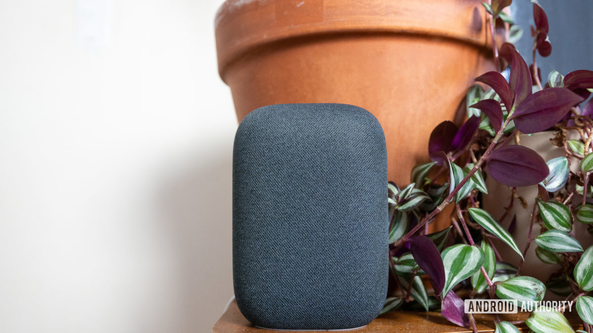 The Google Nest Audio speaker in gray pictured in front of plants on a table