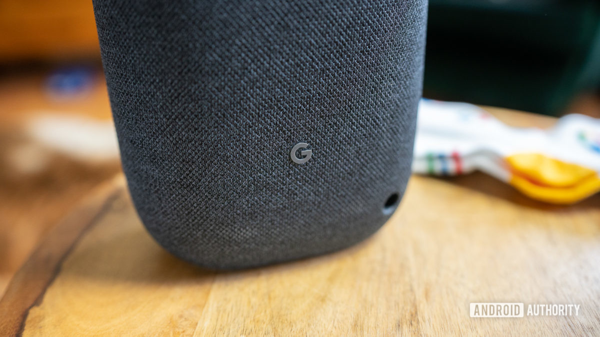 """Pictured is the """"G"""" logo on the back on the Google Nest Audio on a wooden surface"""
