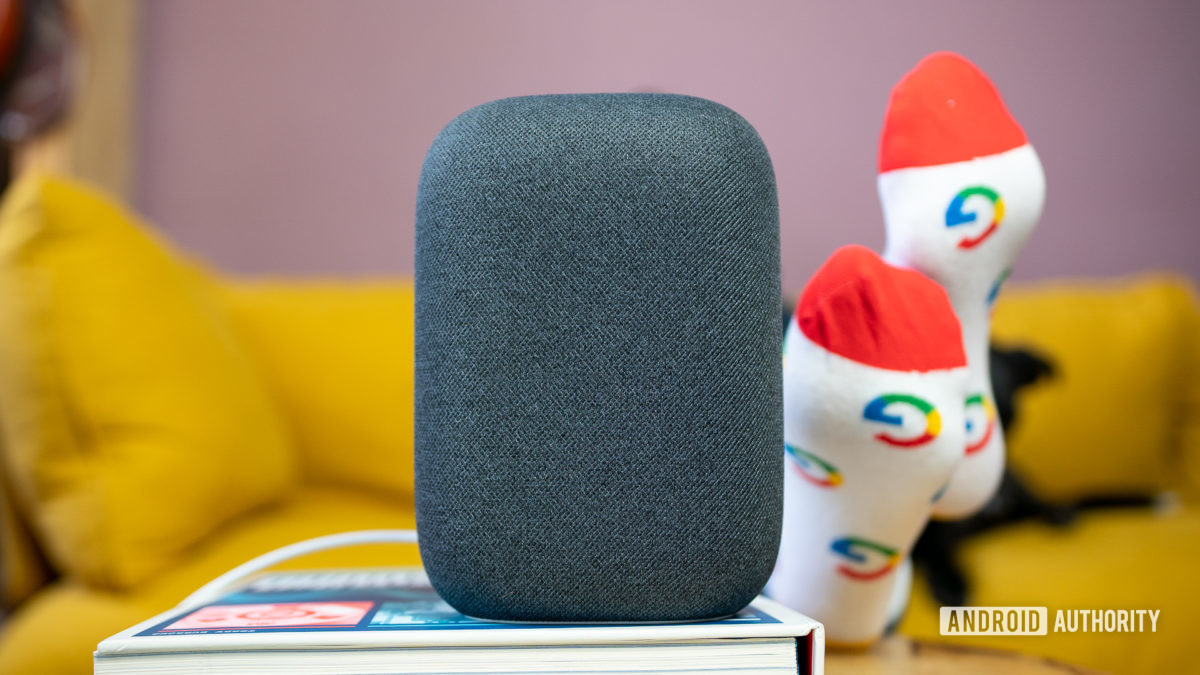 Google Nest Audio in gray on top of book in front of yellow couch.