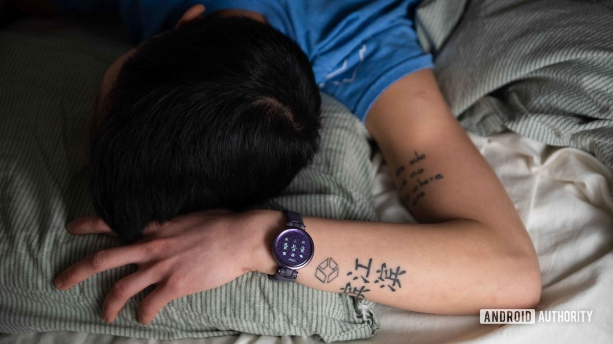 A woman sleeps in bed while she wears the Garmin Lily Sport Edition smart watch on her left wrist.