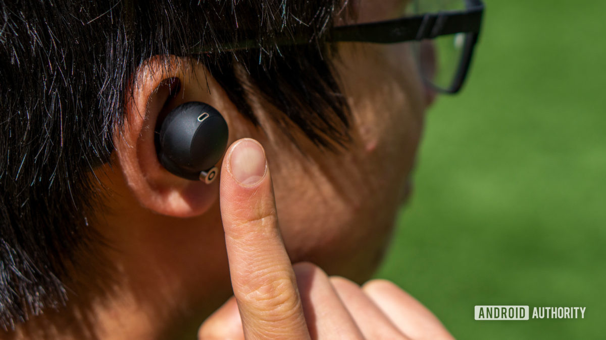 A woman putting her finger up to the Sony WF-1000XM4 earbud.