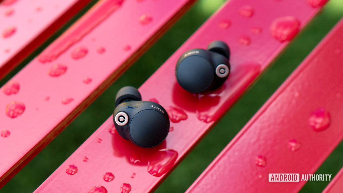 A picture of the Sony WF-1000XM4 earbuds on a wet red bench.