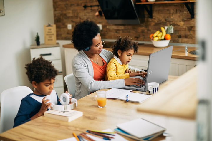 A Black family works on various projects at a dining table. A mother with daughter on her lap works at an Acer computer while a boy adjusts headphones.