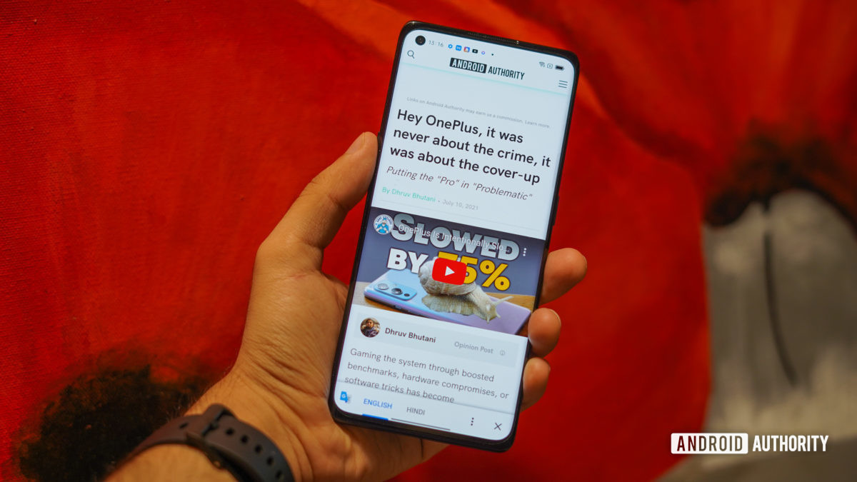 The Oppo Reno 6 Pro review in hand showing the screen with web page open.