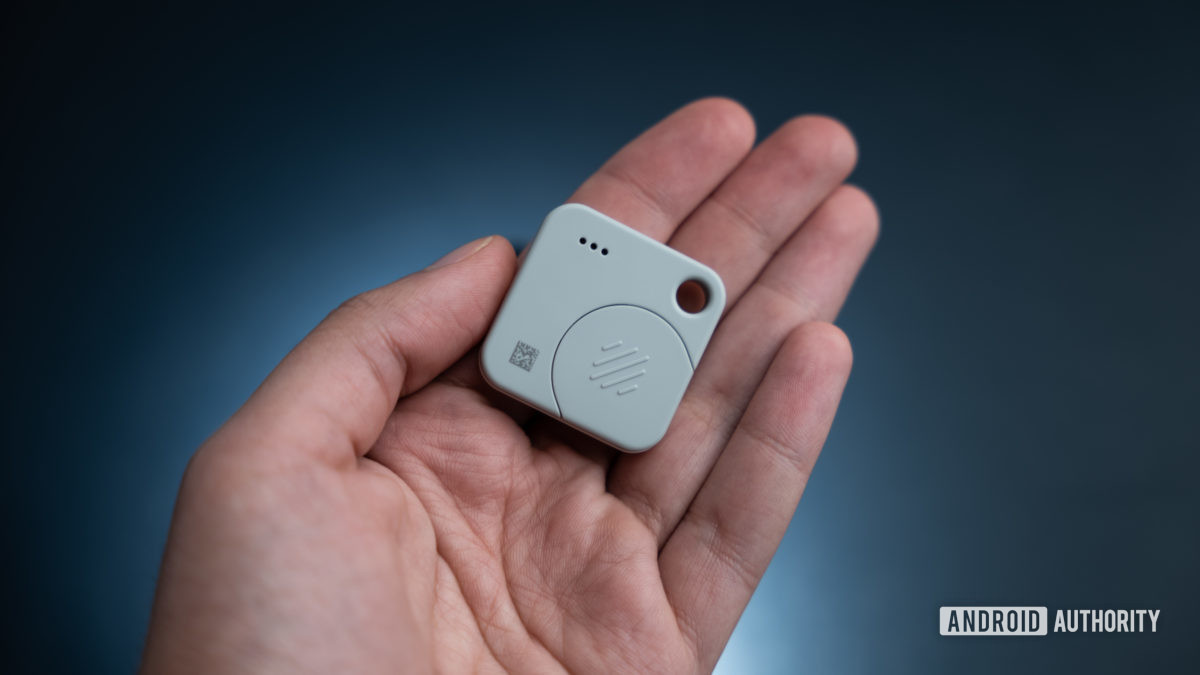 The Tile Mate Tracker rear view in hand showing the battery compartment.