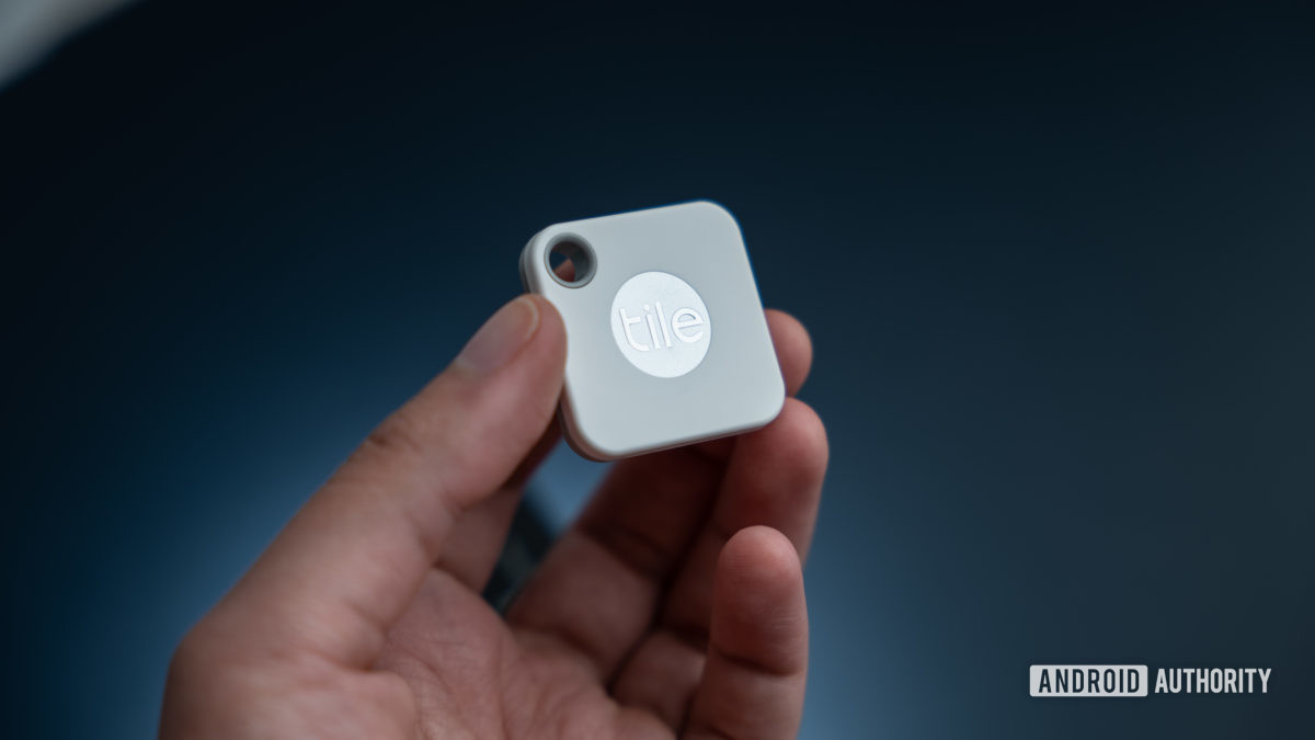The Tile Mate Tracker in hand showing the Tile logo.