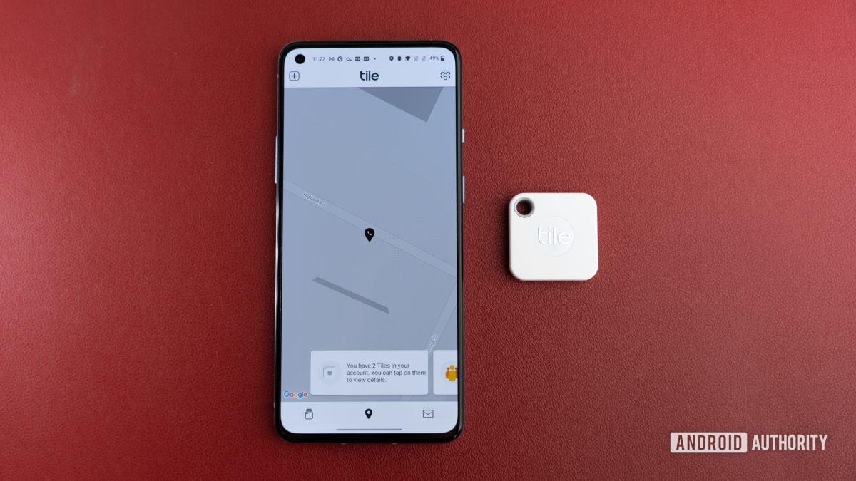 The Tile Mate Tracker next to a phone.