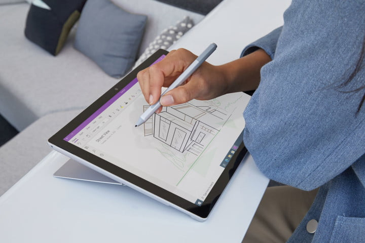 Microsoft surface pro 7 tablet being used as a drawing pad with the touchscreen by a person, hand holding a stylus, sitting at a table in a home setting.