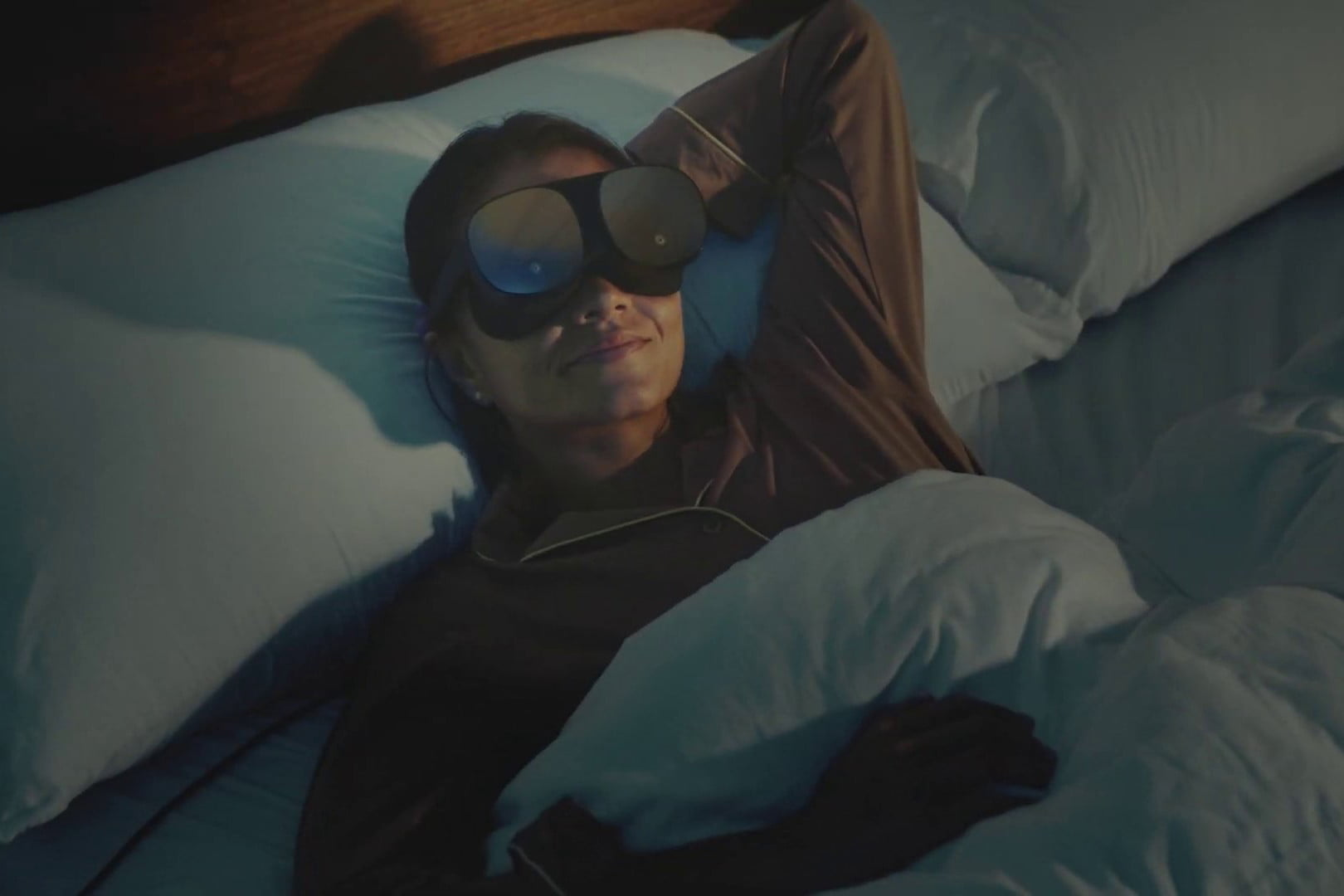Person lying in bed ready to sleep while wearing HTC Vive Flow standalone VR headset.